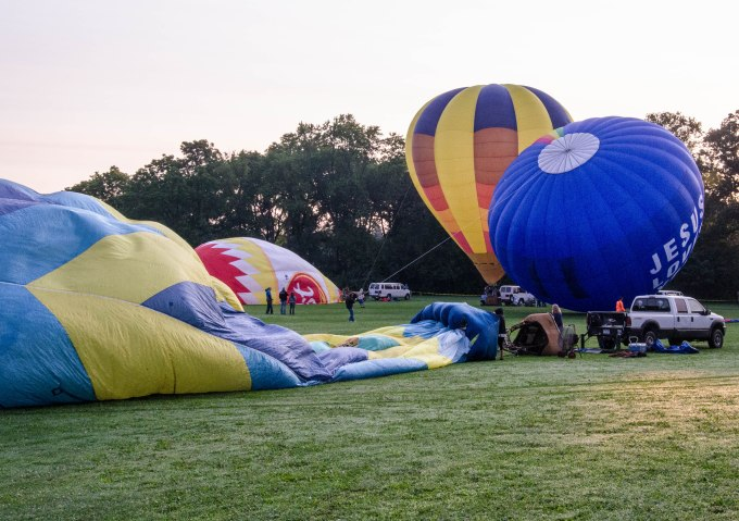 A large fan - powered by a gas-powered generator - begins to fill the balloon with air. The fan to the right will be positioned once the balloon is fully laid out.